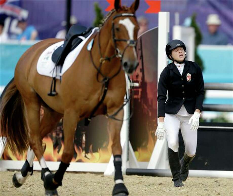 Sarolta Kovacs, of Hungary, gets up after falling off her horse All Rise, during the equestrian show jumping stage of the women's modern pentathlon at the 2012 Summer Olympics, Sunday, Aug. 12, 2012, in London. Photo: AP
