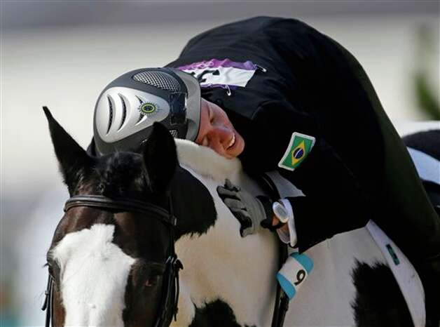 Yane Marques, of Brazil, pats her horse Over The Odds after completing the course in the equestrian show jumping stage of the women's modern pentathlon at the 2012 Summer Olympics, Sunday, Aug. 12, 2012, in London. Photo: AP
