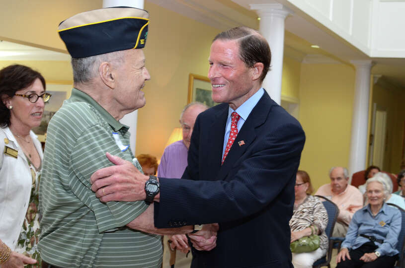 WWII Merchant Marine veteran Dr. Frank Coughlin, of New Canaan, greets United States Senator Richard