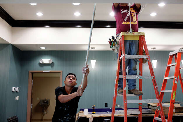 Freddy Fonseca, left, of Pleasanton, paints while Jose Villanueva, of Houston, installs lights as they work to complete the lobby in the newly built Hampton Inn, scheduled to open in early September, in Pleasanton on Wednesday, August 8, 2012. Photo: Lisa Krantz, San Antonio Express-News / San Antonio Express-News