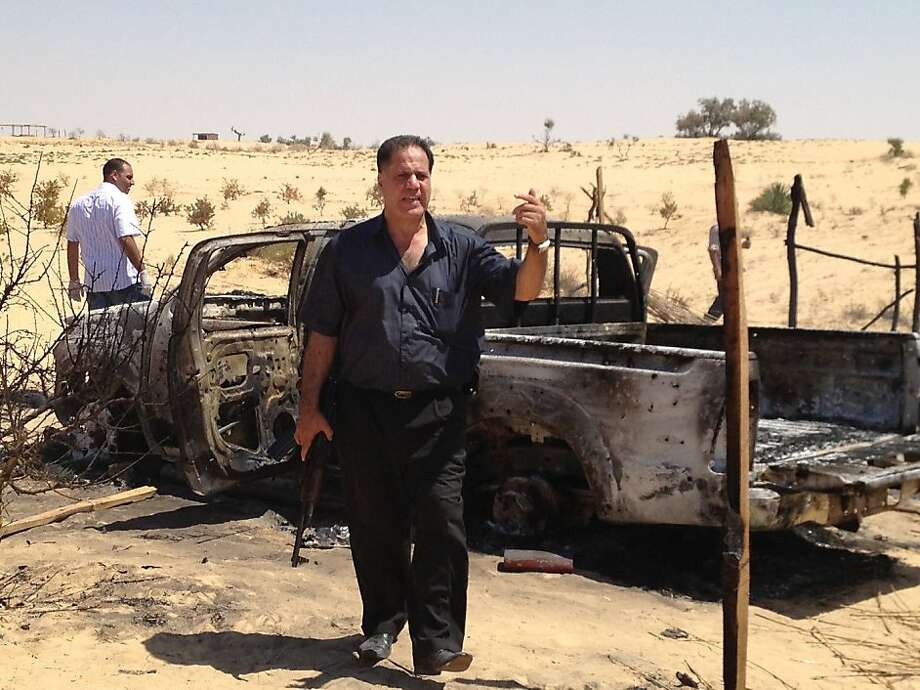 Egyptian Gen. Mohammed Khalid gestures in front of a charred truck tied to an Aug. 5 attack that killed 16 soldiers. A raid targeting suspects in the attack killed seven men Sunday. Photo: Nancy A. Youssef, McClatchy-Tribune News Service