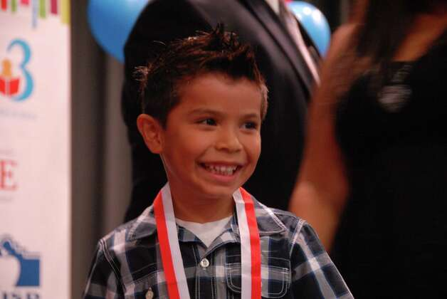 Aidan Medina of the Harlandale school district smiles as he receives a certificate and medal Aug. 3 after completing H-E-BÕs Family Literacy Program. Photo: Courtesy Photo