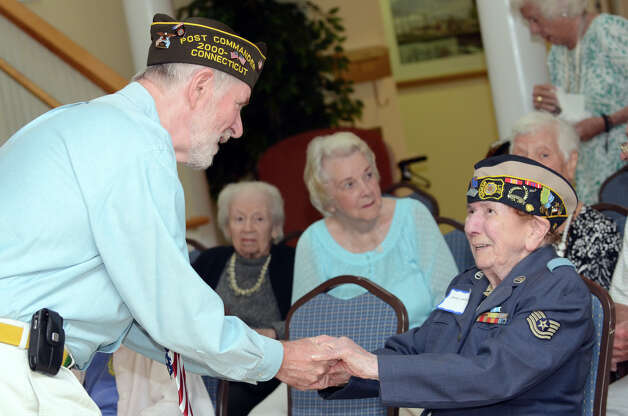Phillip Kraft, Commander of Darien VFW Post 6933, greets WWII veteran Jennie Lombardi, a resident of Atria Senior Living facility in Darien, during the observation of the 67th anniversary of the end of WWII at Atria on Sunday, Aug. 12, 2012. Photo: Amy Mortensen / Connecticut Post Freelance