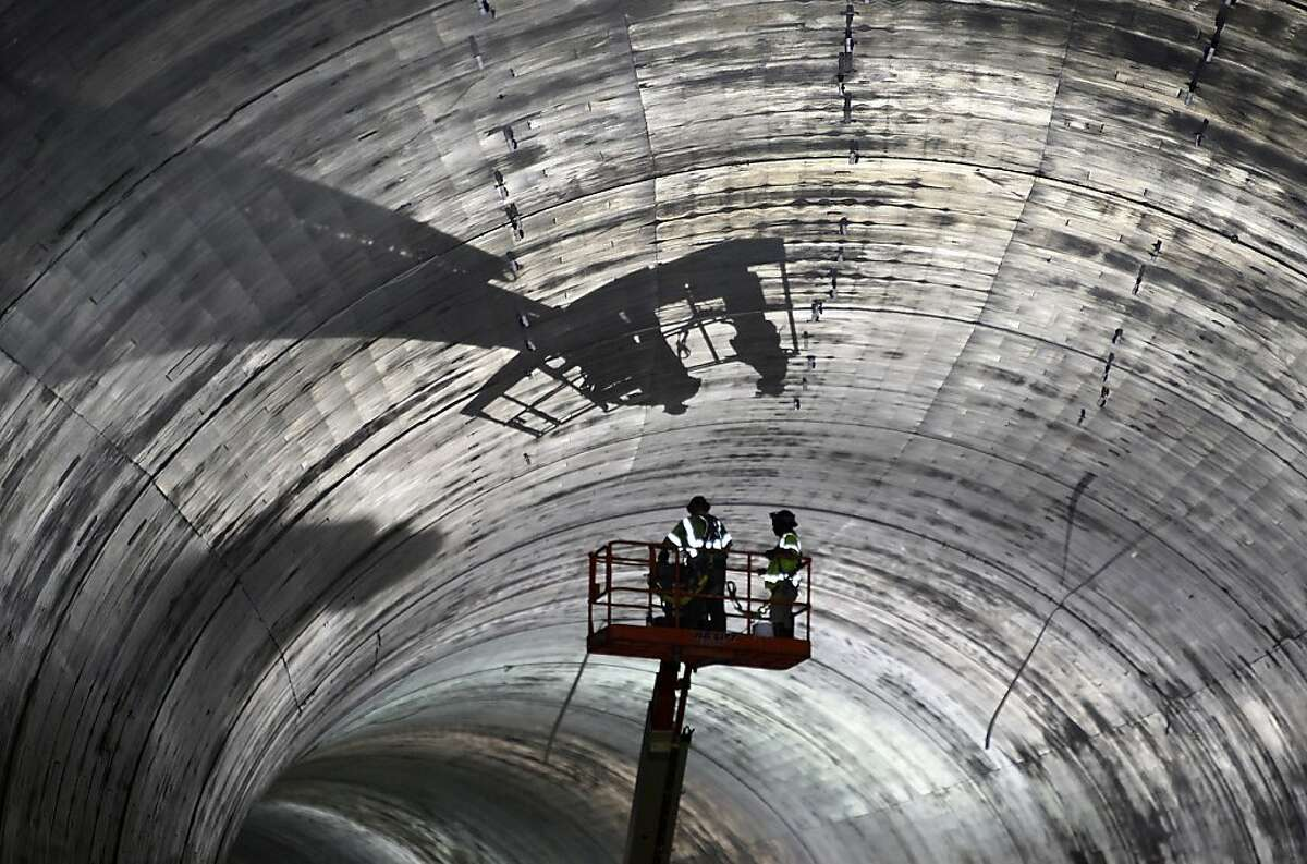 A crew works near the ceiling inside the fourth bore the Caldecott Tunnel, currently under construction, in Oakland, Calif. on Thursday, Aug. 9, 2012.