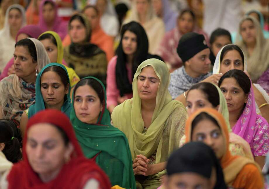 People attend a prayer service at the Sikh Temple of Wisconsin in Oak Creek, Wis., Sunday, Aug. 12, 2012. More than 100 people gathered for the first Sunday prayer service since a white supremacist shot and killed six people there before fatally shooting himself. (AP Photo/Jeffrey Phelps) Photo: JEFFREY PHELPS / FR59249 AP