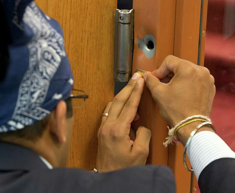 "A bullet hole on a door frame is left as a remembrance inside the Sikh Temple of Wisconsin in Oak Creek, Wis., Sunday, Aug. 12, 2012. After this photo was made, the hole was marked with a small gold plate engraved  with ""We Are One. 8-5-12."" (AP Photo/Jeffrey Phelps) Photo: JEFFREY PHELPS, Associated Press / FR59249 AP"