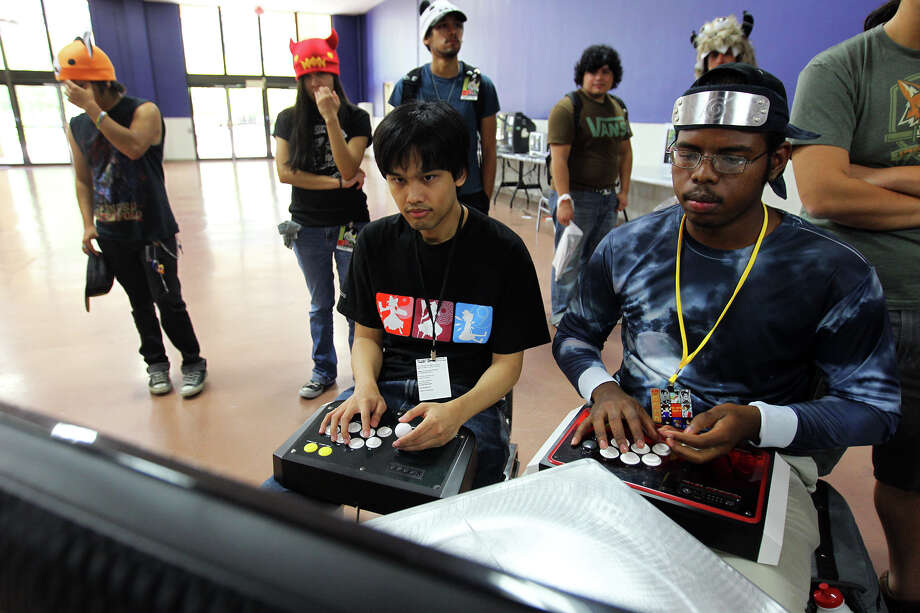 Wes Mojica, left, and Dominic Heningburg play the newly released P4A Persona 4 Arena game on a Play Station 3 during San Japan at the Henry B. Gonzalez Convention Center, Sunday, August 12, 2012. (JENNIFER WHITNEY) Photo: JENNIFER WHITNEY, Special To The Express-News / © Jennifer Whitney