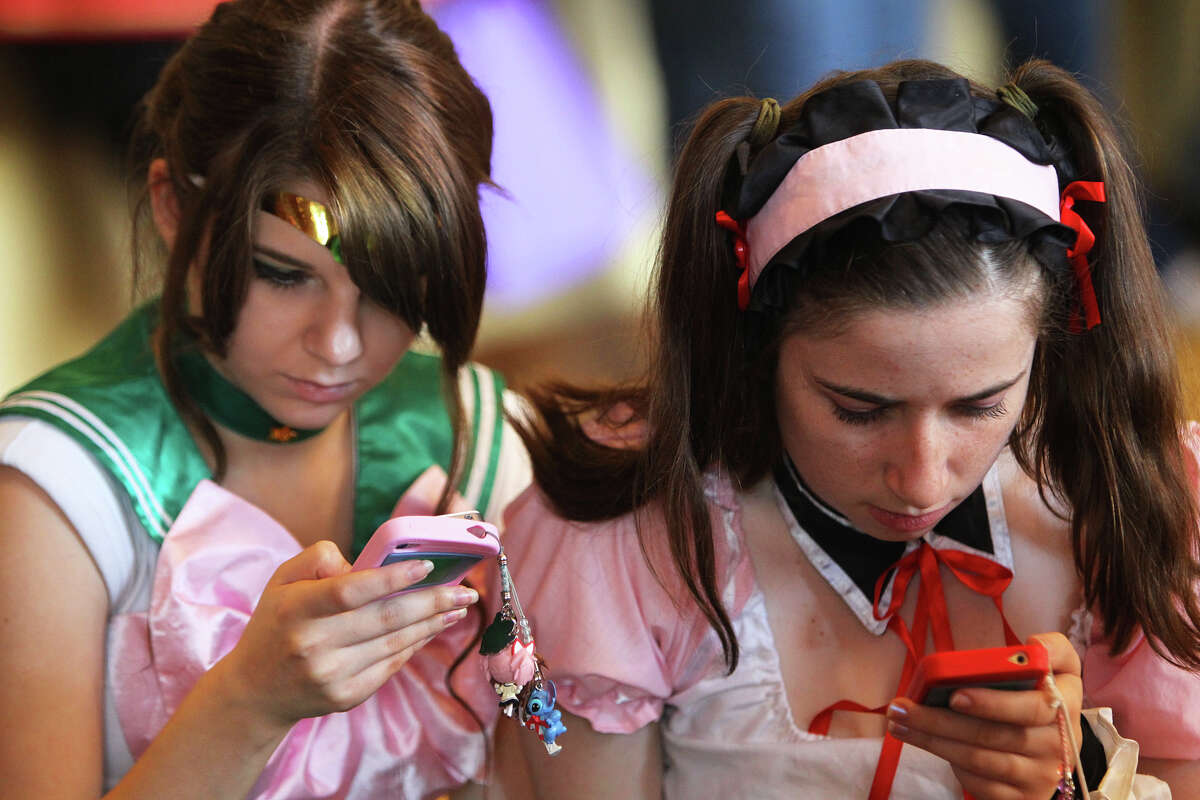 Shanna Francis dressed as Sailor Jupiter from Sailor Moon and her friend, Kalie Gallaher (ck) dressed as Mikuru Asaltina from The Melancholy of Haruhi Suzumya play on their iPhones during San Japan at the Henry B. Gonzalez Convention Center, Sunday, August 12, 2012. (JENNIFER WHITNEY)