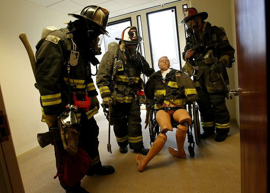 San Francisco firefighters in a large-scale high-rise drill lead a mannequin representing a burn victim in a wheelchair to safety. Photo: Brant Ward, The Chronicle