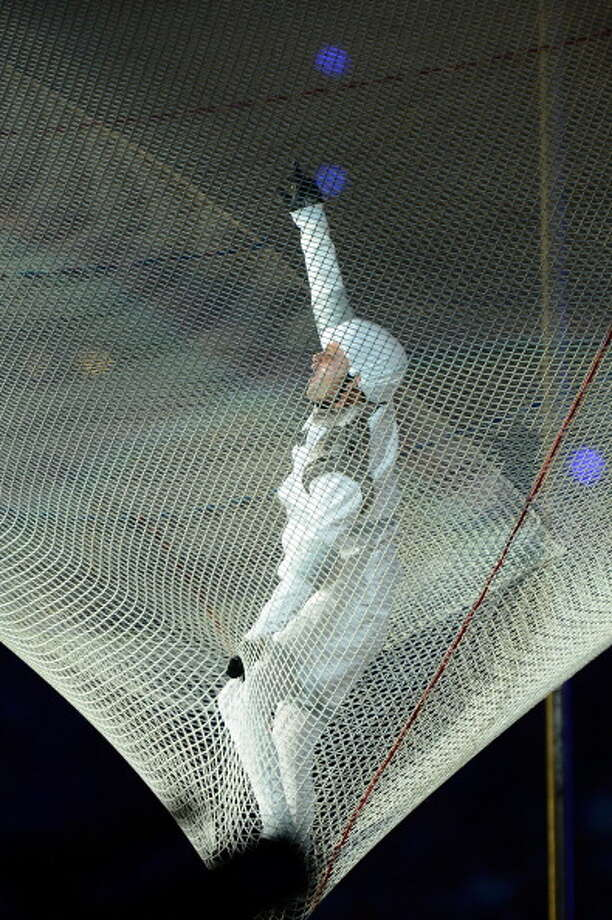 A human cannonball performs during the Closing Ceremony. Photo: Getty Images
