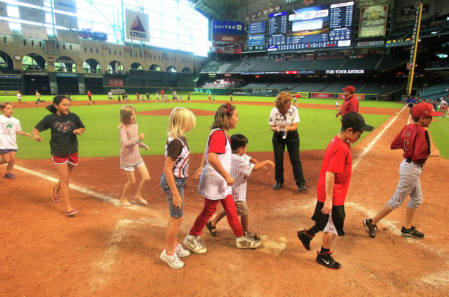 Children run the bases after a baseball game between the Houston Astros and the Milwaukee Brewers at Minute Maid Park Sunday, Aug. 12, 2012, in Houston. The Brewers won 5-3. (Cody Duty / Houston Chronicle) Photo: Cody Duty / © 2011 Houston Chronicle