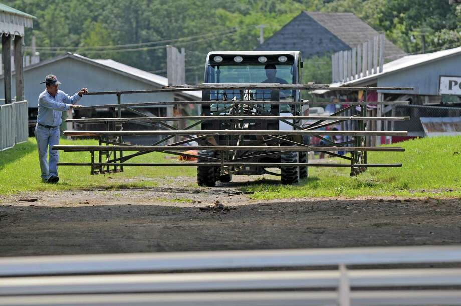 Workers move bleachers for a showing area at the sheep barn in preparation for the Tuesday beginning of The Altamont Fair, on Sunday Aug. 12, 2012 in Altamont, NY.  (Philip Kamrass / Times Union) Photo: Philip Kamrass / 00018808A