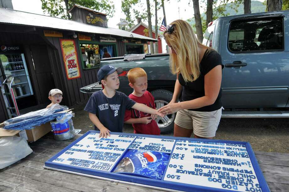Rebecca Reville of Selkirk and her son Eddie, 6,  second from left, and his cousin Brady Engel, 7, second from right, set up a menu board for their family's restaurant, The Sap Bucket,  in preparation for the Tuesday beginning of The Altamont Fair, on Sunday Aug. 12, 2012 in Altamont, NY.  Cody Reville, 4, is at far left.  (Philip Kamrass / Times Union) Photo: Philip Kamrass / 00018808A