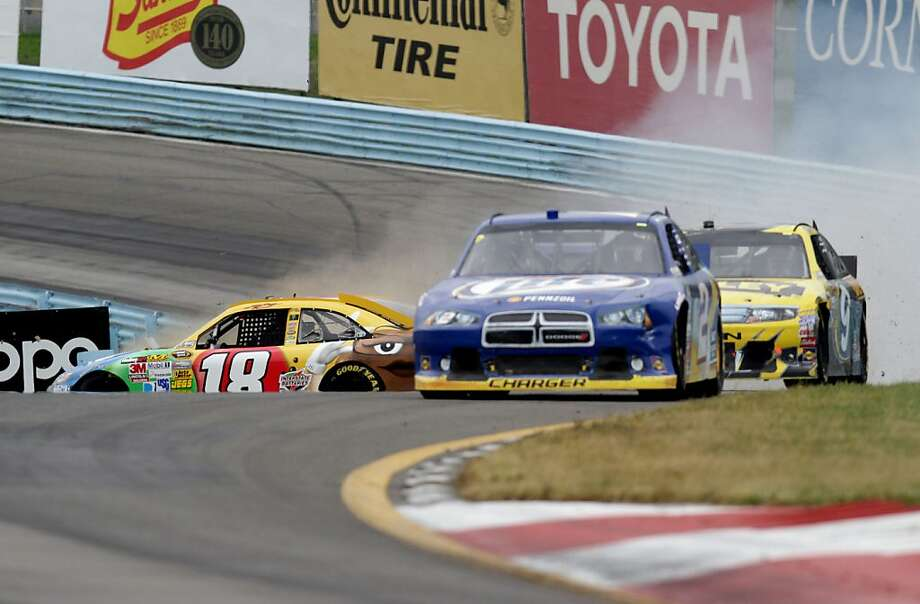 Kyle Busch (18) skids after hitting oil on the final lap, opening the door for Brad Keselowski (front) and Marcos Ambrose. Photo: Jerry Markland, Getty Images For NASCAR