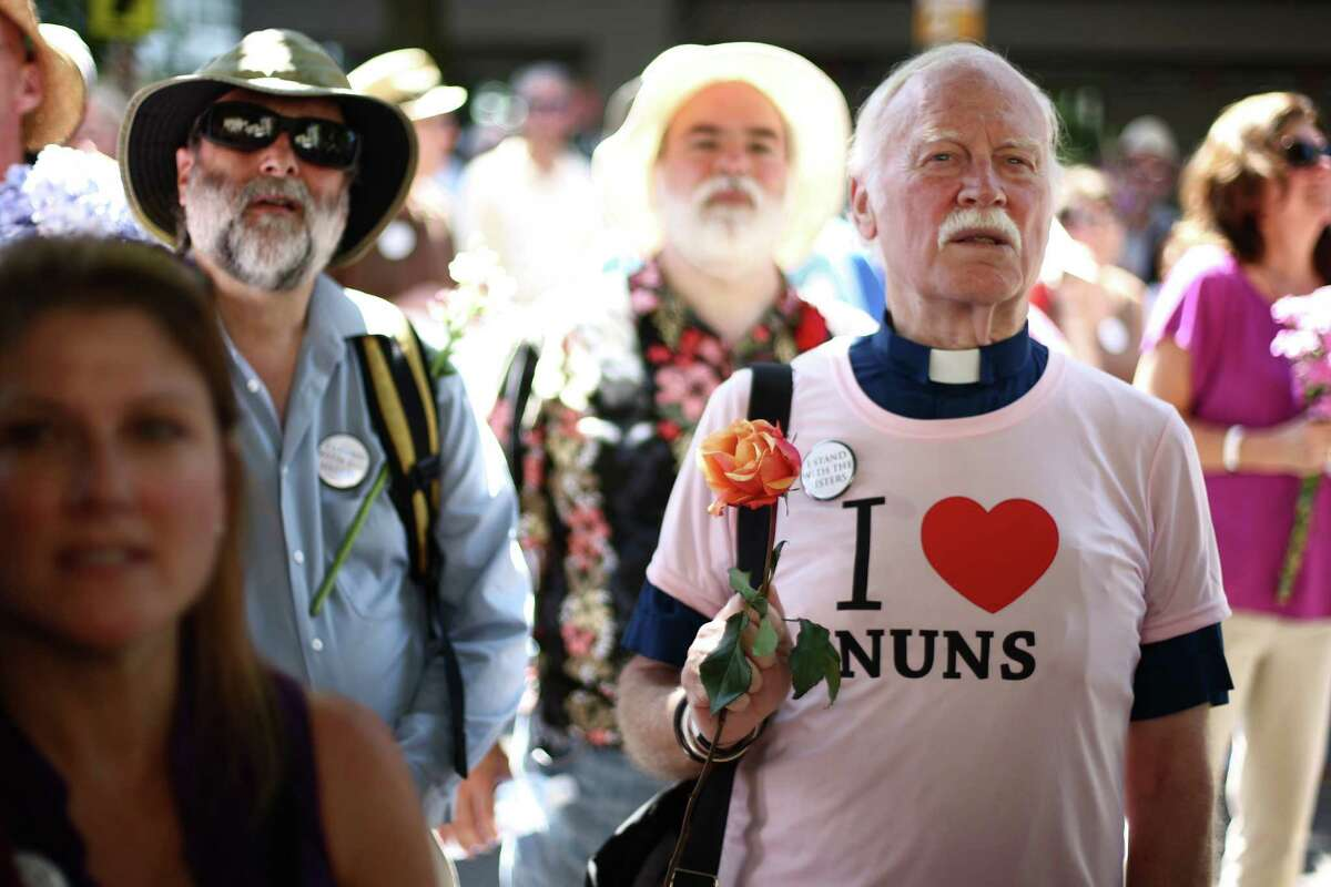 Rev. Joshua Liljenstolpe, right, holds a flower as hundreds of people gather on the steps of Saint James Cathedral in Seattle on Sunday, August 12, 2012. Hundreds of people came out to support Catholic nuns on the steps of Saint James Cathedral, the episcopal seat of Archbishop Peter J. Sartain, the Roman Catholic bishop tasked by the Vatican to oversee nuns in the U.S.
