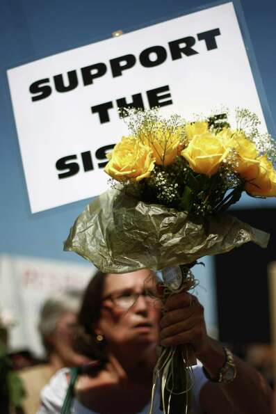 People carry signs and flowers as they march to support Catholic nuns.