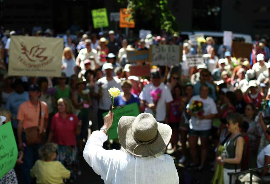 MHB Conant holds up a flower as hundreds of people gather in front of Saint James Cathedral. Photo: JOSHUA TRUJILLO / SEATTLEPI.COM