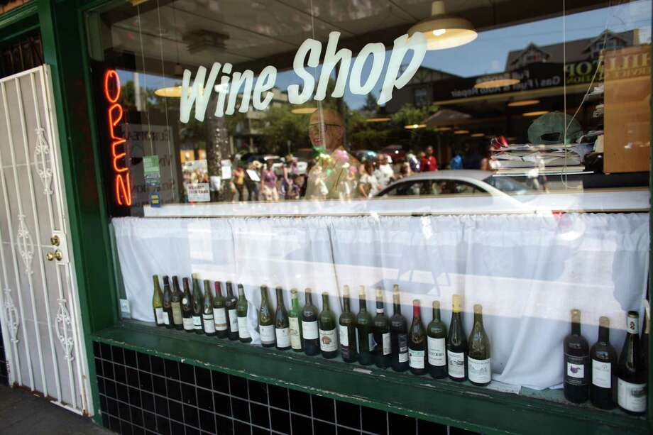 Doug Nufer watches from his Wine Shop of 15th Avenue as hundreds of people gather and march through Capitol Hill and First Hill to Saint James Cathedral. Photo: JOSHUA TRUJILLO / SEATTLEPI.COM