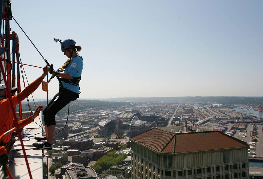 Jill Morgan rappels off of the top of Seattle's 1000 2nd Avenue Building during the Special Olympics Over The Edge event on Sunday, Aug. 12, 2012. Participants of the Over the Edge event fundraised money for the Special Olympics while rappelling 40 stories off of a building. (Photo by Sofia Jaramillo) Photo: Sofia Jaramillo, Seattlepi.com Photos / SEATTLEPI.COM