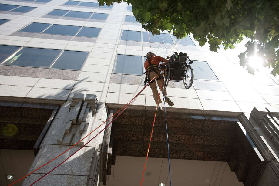 Dale Doornek, a paraplegic from Sultan, Washington, and a professional reach the last stretch of a fourty story rappel during the Special Olympics Over The Edge event on Sunday, Aug. 12, 2012. Participants of the Over the Edge event fundraised money for the Special Olympics while rappelling 40 stories off of a building. (Photo by Sofia Jaramillo) Photo: Sofia Jaramillo, Seattlepi.com Photos / SEATTLEPI.COM