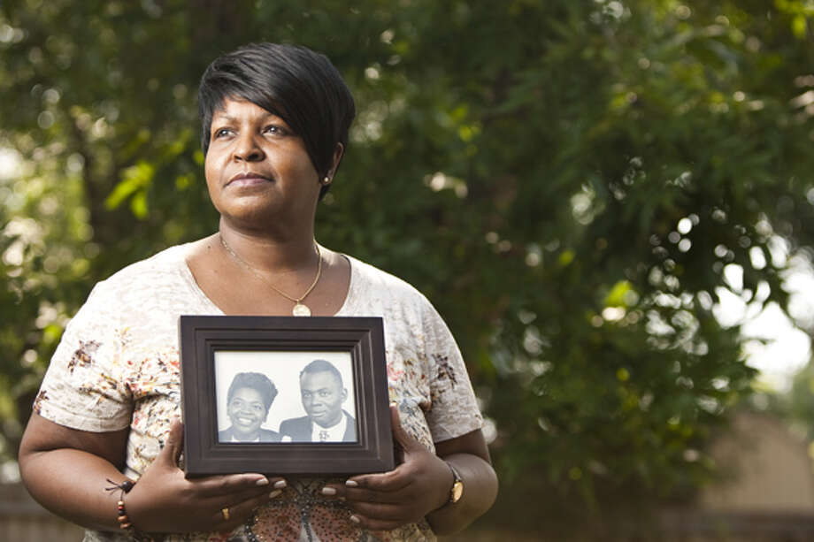 Darlene Sims holds a picture of her parents Mattie Catherine Sims and Theodore Sims Sr.,  Aug. 10, 2012, in Houston as she talks about property that was stolen from her family. Photo: Nick De La Torre, . / © 2012  Houston Chronicle