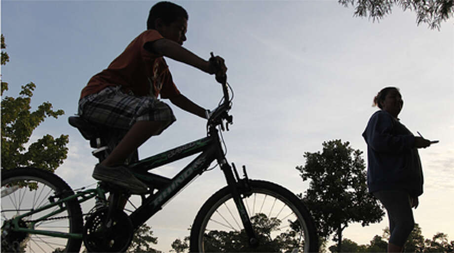 Andres Arredondo , 7, rides his bike early in the morning at Nob Hill Park.  Sunny and high temperatures are expected today.  Photo: (Mayra Beltran / Chronicle)
