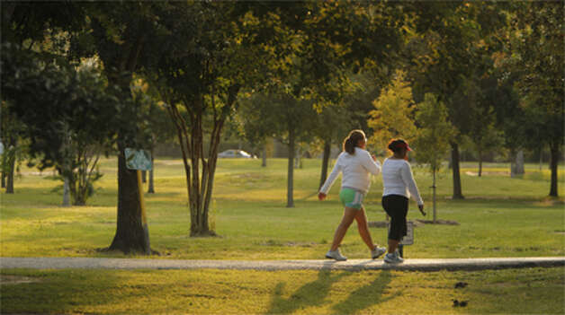 Yeni Hernandez and Sonia Ortega beat the heat by power walking early in the morning at Nob Hill Park on Aug.13, 2012 in Houston.  Photo: (Mayra Beltran / Chronicle)