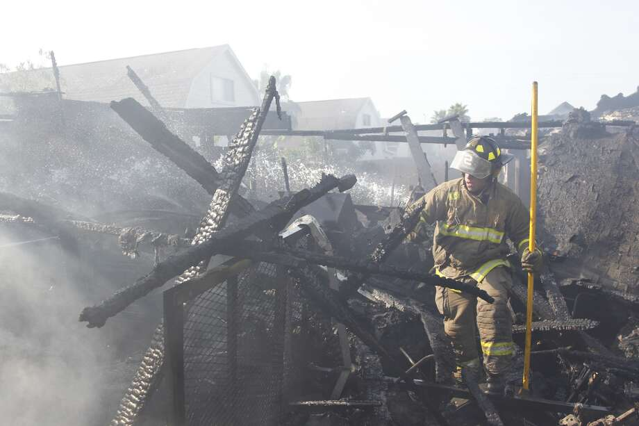 Pasadena firefighters work to extinguish a house fire that damaged an entire home on Aug. 13, 2012 in Pasadena, Tx. Photo: Houston Chronicle, Mayra Beltran
