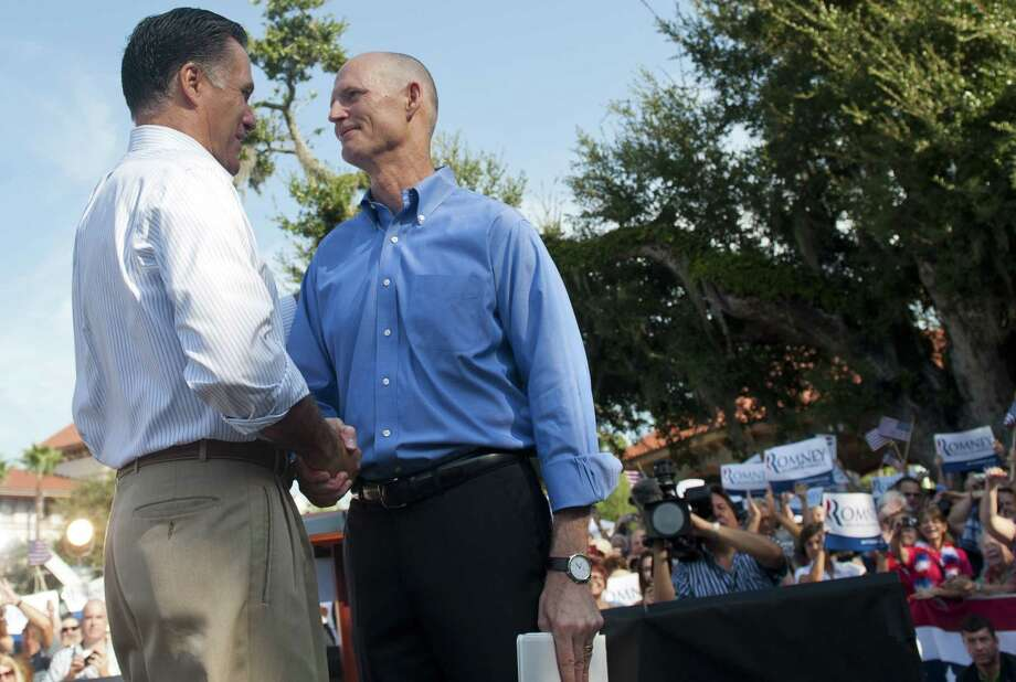 US Republican presidential candidate and former Massachusetts Governor Mitt Romney (L) shakes hands with Florida Governor Rick Scott during a campaign rally at Flagler College in St. Augustine, Florida, August 13, 2012. Romney and his running mate Wisconsin Congressman Paul Ryan will take their re-energized presidential campaign to two key states on Monday, seeking to persuade voters that they can restore America's economic might. Romney campaigns in Florida while Ryan heads to Iowa, both battleground states which may decide the outcome of the November 6 presidential election.AFP PHOTO / Saul LOEBSAUL LOEB/AFP/GettyImages Photo: SAUL LOEB, AFP/Getty Images / AFP