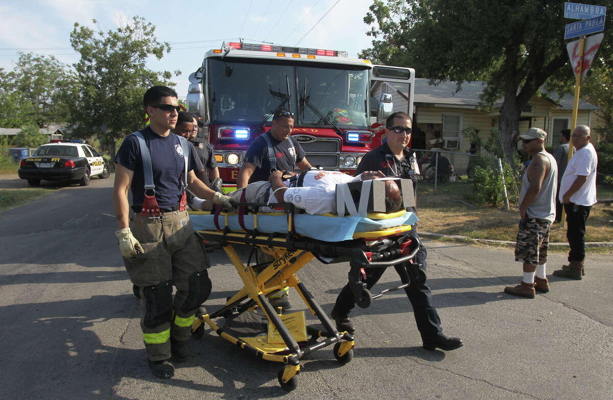 San Antonio firefighters prepare to transport a man who crashed his minivan into the side of a house located on the corner of Alhambra and Santa Paula shortly after 9:00 a.m. Monday August 13, 2012. Nobody inside of the home was harmed. The cause of the crash is being investigated. John Davenport/2012©San Antonio Express-News