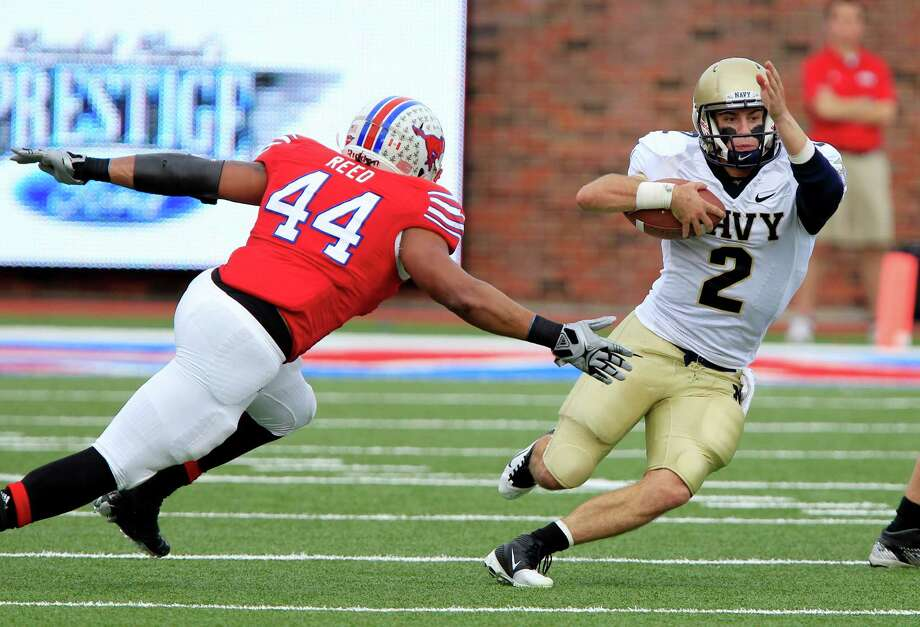 Navy quarterback Kriss Proctor (2) scrambles for yardage, as SMU linebacker Taylor Reed (44) tries to make the stop during the first quarter of their NCAA college football game on Saturday, Nov. 12, 2011, at Gerald J. Ford Stadium in Dallas, Texas. Navy won 24-17. (AP Photo/John F. Rhodes) Photo: John F. Rhodes, FRE / AP2011