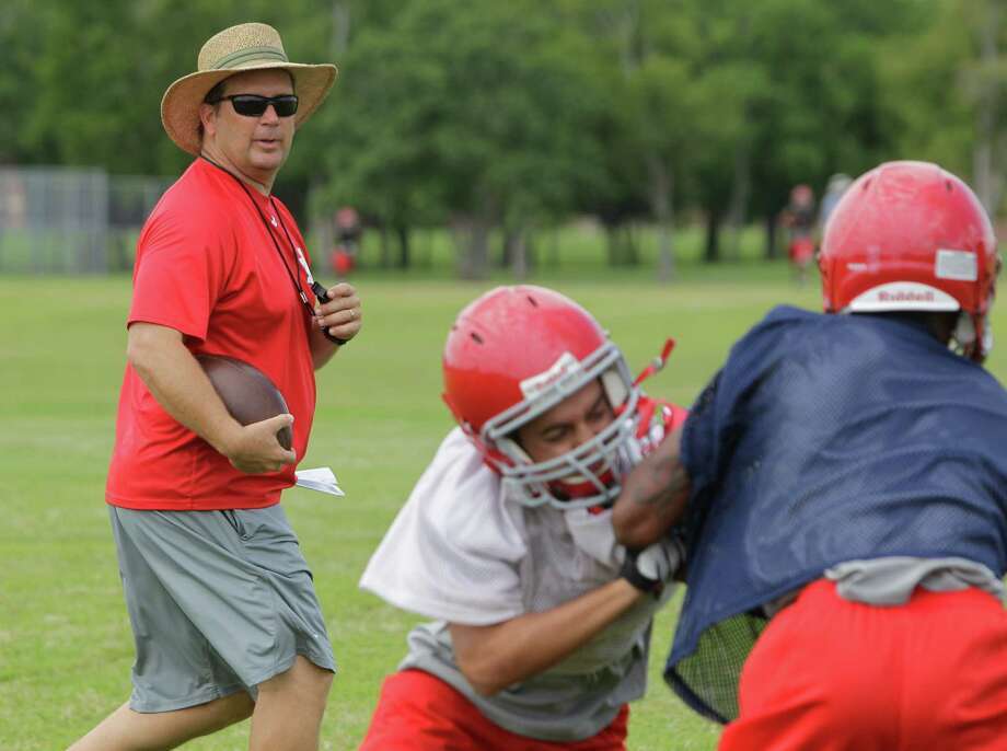 Alief Taylor High School football coach J. D. Jordan watches players run drills during first day of practice Monday, Aug. 13, 2012, in Houston. Photo: Melissa Phillip, Houston Chronicle / © 2012 Houston Chronicle