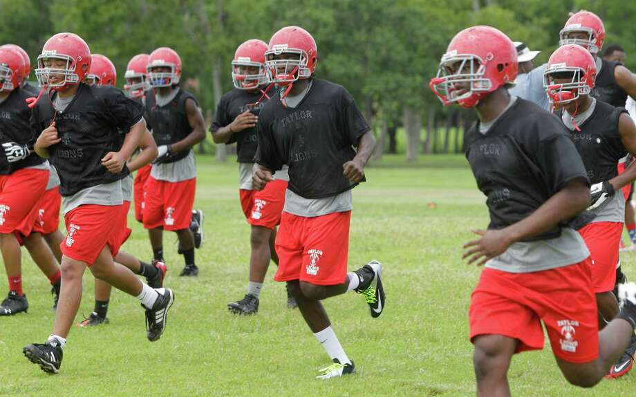 Alief Taylor High School football player Torrodney Prevot, shown in center, among other players as they run during first day of practice Monday, Aug. 13, 2012, in Houston. Photo: Melissa Phillip, Houston Chronicle / © 2012 Houston Chronicle