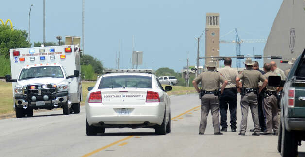 Texas State troopers and Brazos Valley lawmen watch as an ambulance believed to be carrying one of their downed fellow officers speeds off to a hospital in College Station, Texas, Monday, Aug. 13, 2012. Police say at least one law enforcement officer and one civilian have been killed in a shooting near Texas A&M University's campus. Assistant Chief Scott McCollum says the gunman also was shot Monday before being taken into custody.  (AP Photo/Bryan-College Station Eagle, Dave McDermand) Photo: Dave McDermand, Associated Press / College Station Eagle