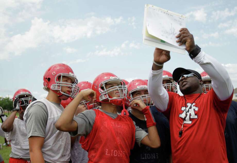 Alief Taylor High School offensive football coach Mike Arogbonio shows players a play during first day of practice Monday, Aug. 13, 2012, in Houston. Photo: Melissa Phillip, Houston Chronicle / © 2012 Houston Chronicle