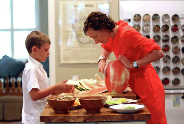 CIA chef-instructor Elizabeth Johnson-Kossick cuts a watermelon as her son Nick Kossick watches. Photo: Helen L. Montoya, San Antonio Express-News / ©SAN ANTONIO EXPRESS-NEWS