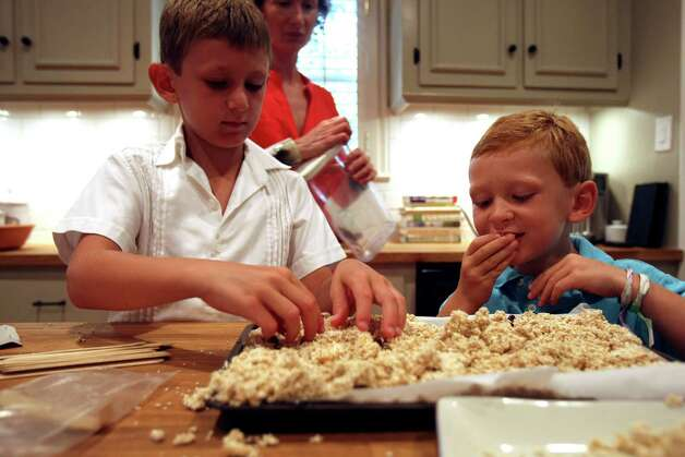 CIA chef-instructor Elizabeth Johnson-Kossick watches as her sons Nick Kossick, 7 and Ted Kossick, 6 sample some snacks. Photo: Helen L. Montoya, San Antonio Express-News / ©SAN ANTONIO EXPRESS-NEWS