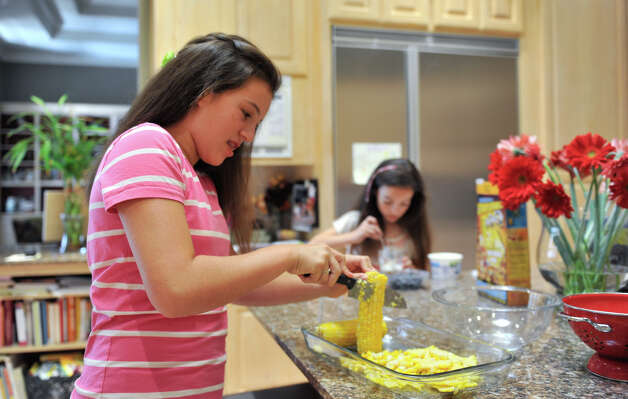 Sophie Cantu (left) and her sister, Iliana, prepare healthy snacks in the family kitchen. Photo: Robin Jerstad, For The Express-News