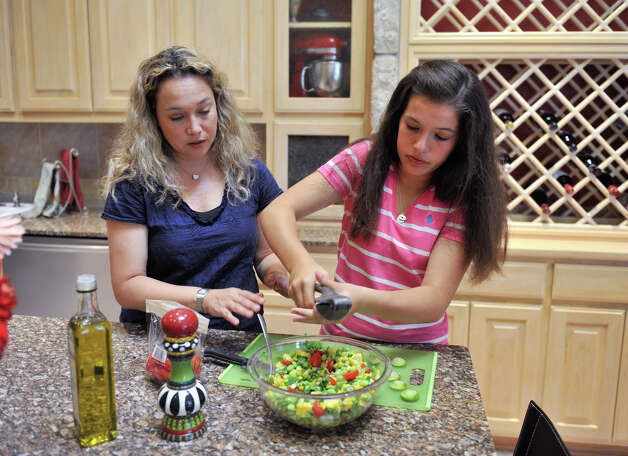 Aliza Holzman-Cantu (left) and her daughter, Sophie, make a healthy, fresh salad. Photo: Robin Jerstad, For The Express-News