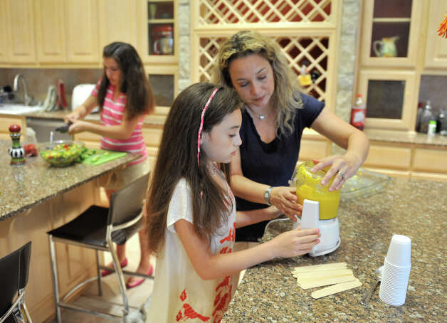 Iliana Cantu works with her mother, Aliza Holzman-Cantu makes Mango popsicles as her sister, Sophie, makes a fresh salad. Photo: Robin Jerstad, For The Express-News