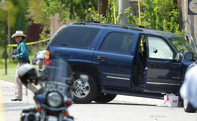 An investigator photographs a vehicle which was struck by a bullet near the scene where a gunman opened fire near the Texas A&M univerity on Monday, Aug. 13, 2012, in College Station. Photo: Mayra Beltran, Houston Chronicle / © 2012 Houston Chronicle