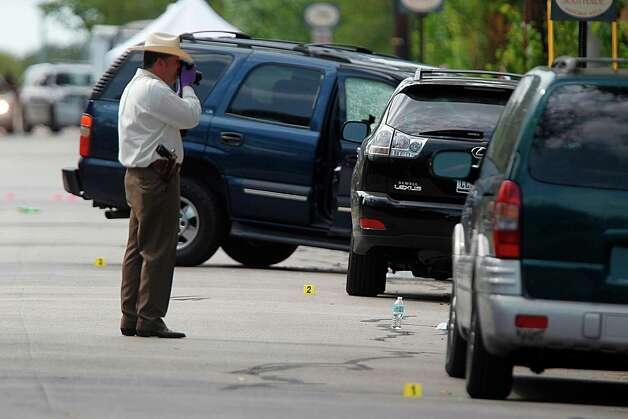 Investigator photographs evidence on the floor and vehicles near the scene where a gunman opened fire near the Texas A&M univerity on Monday, Aug. 13, 2012, in College Station. Photo: Mayra Beltran, Houston Chronicle / © 2012 Houston Chronicle