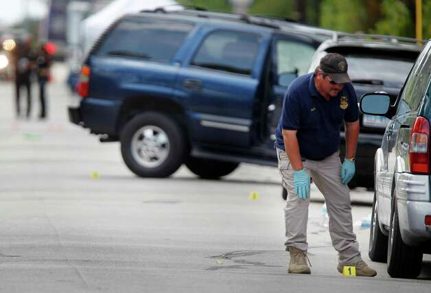 ATF investigator walk near a vehicle which was struck by a bullet near the scene where a gunman opened fire near the Texas A&M univerity on Monday, Aug. 13, 2012, in College Station. Photo: Mayra Beltran, Houston Chronicle / © 2012 Houston Chronicle