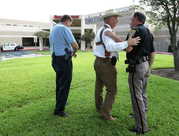 Brazos County Sheriff Chris Kirk, center, is comforted by other officers of the law after he spoke to the media outside of the College Station Medical Center, Monday, Aug. 13, 2012, in College Station, where five victims were brought, including Constable Pct. 1's Brian Bachmann, who was killed following a shooting near the Texas A&M campus. Photo: Karen Warren, Houston Chronicle / © 2012  Houston Chronicle