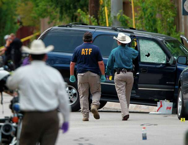 ATF and other investigators walk near a vehicle which was struck by a bullet near the scene where a gunman opened fire near the Texas A&M univerity on Monday, Aug. 13, 2012, in College Station. Photo: Mayra Beltran, Houston Chronicle / © 2012 Houston Chronicle