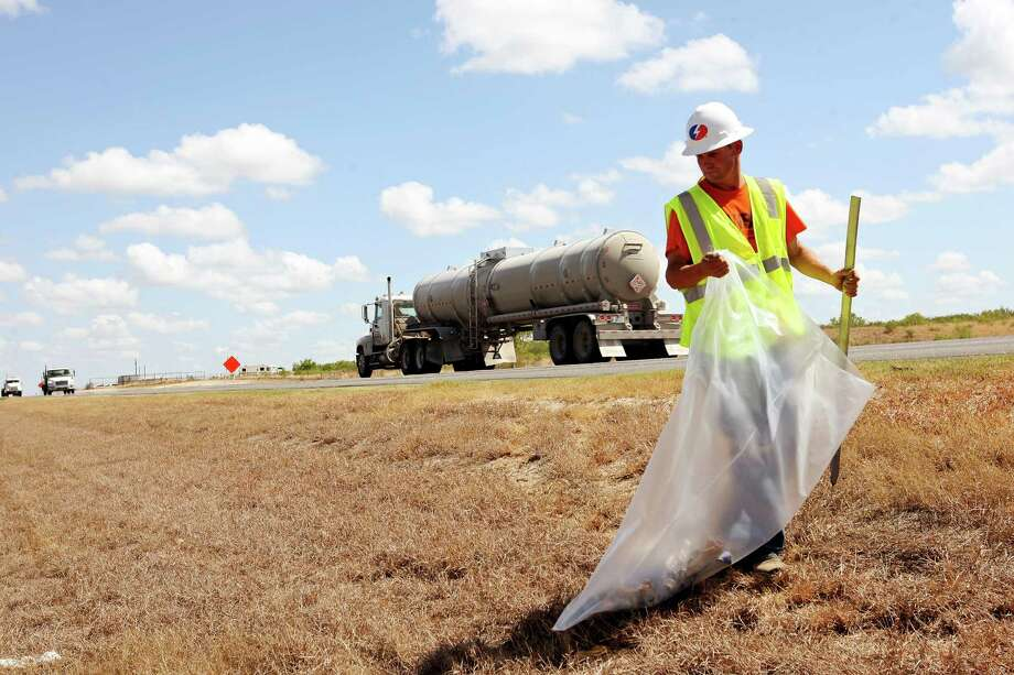 Cal Cochran picks up trash along State Highway 16 just north of Tilden, Texas, Thursday, August 9, 2012. The area is in the Eagle Ford Shale play and Tilden has seen an increase in oil related companies opening field offices near the town. Photo: Jerry Lara, San Antonio Express-News / © 2012 San Antonio Express-News