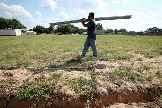 "Alberto Flores, 31, lays pipe for electrical lines in a staked out field in Pleasanton, Texas, Wednesday, August 8, 2012. The 43-slot lot is part of the Hwy 97 RV Park. ""We have people calling us every day,"" say park owner, Robert Fuselier. It is expected that the park will be filled within a month after opening. Photo: Jerry Lara, San Antonio Express-News / © 2012 San Antonio Express-News"