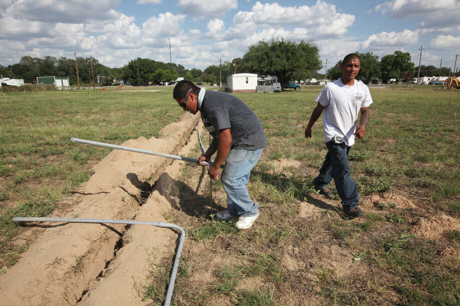 "Alberto Flores, 31, left, and Valdemar Herrera, 24, lay pipe for electrical lines in a staked out field in Pleasanton, Texas, Wednesday, August 8, 2012. The 43-slot lot is part of the Hwy 97 RV Park. ""We have people calling us every day,"" say park owner, Robert Fuselier. It is expected that the park will be filled within a month after opening. Photo: Jerry Lara, San Antonio Express-News / © 2012 San Antonio Express-News"