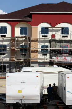 At the end of the work day, construction workers hang out by their living quarters in front of the hotel they are building in Pleasanton, Texas, Wednesday, August 8, 2012. Demands for housing driven by the Eagle Ford oil and gas play is up in small towns like Pleasanton and others throughout the area. Photo: Jerry Lara, San Antonio Express-News / © 2012 San Antonio Express-News