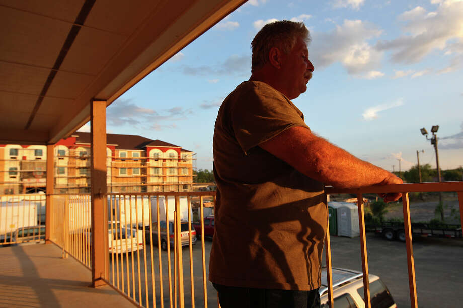 Mike McCormack, 58, takes a smoke break outside his room at the Super 8 in Pleasanton, Texas, Wednesday, August 8, 2012. Behind him is a Best Western under construction to accommodate demands for housing from the oil and gas industry. McCormack works for a company building bases for communication towers. Photo: Jerry Lara, San Antonio Express-News / © 2012 San Antonio Express-News